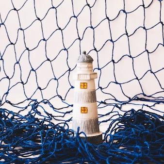 Composição marinha com farol e rede de pesca