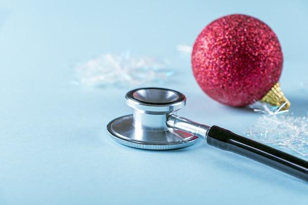 Composição médica de ano novo com estetoscópio e decoração de natal, bugiganga sobre fundo azul