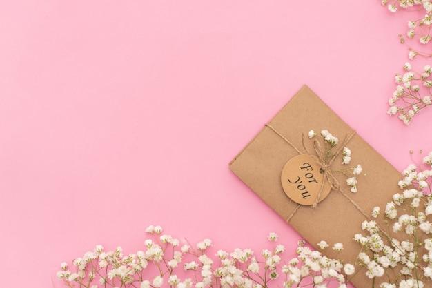 Composição mínima com um envelope rosa, cartão branco em branco e uma flor de cera