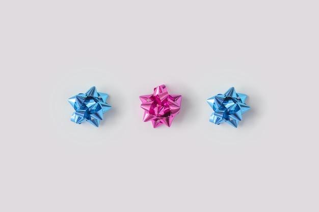 Composição mínima de arcos decorativos de plástico rosa e azuis para presentes de natal.