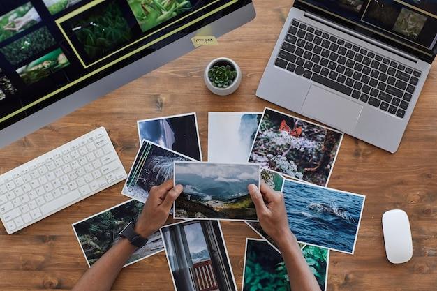 Composição mínima de fundo de mãos masculinas segurando fotografias impressas sobre uma mesa de madeira texturizada, conceito de escritório de fotógrafos, espaço de cópia