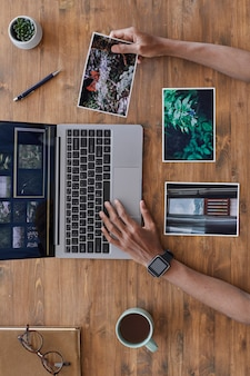 Composição mínima de fundo de mãos masculinas segurando fotos impressas e usando laptop em mesa de madeira texturizada, escritório de fotógrafos, espaço de cópia