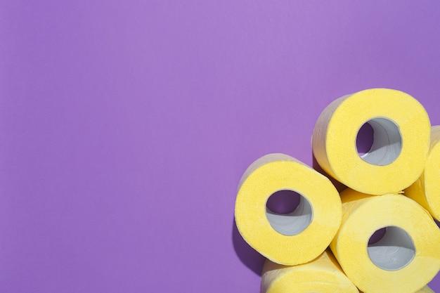 Composição minimalista com padrão de papel higiênico amarelo brilhante rola sobre fundo roxo.