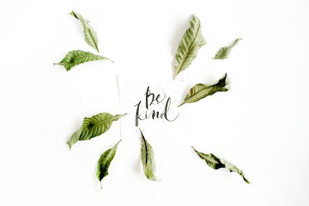 Composição minimalista com palavras be kind escritas em estilo caligráfico em papel com moldura de folha na superfície branca