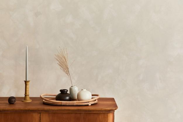 Composição minimalista da sala de estar com cômoda de madeira, abajur, flores secas em um vaso, livro, decoração e acessórios pessoais elegantes na decoração elegante da casa. modelo. copie o espaço.