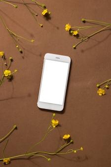 Composição minimalista da vida do marrom bege com flores silvestres e tecnologia - telefone celular, flor amarela, conceito de design de arte moderna abstrata, vista superior