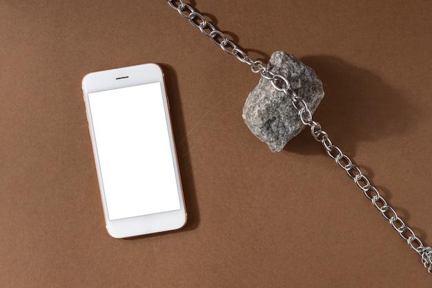 Composição minimalista da vida do marrom bege com material natural e tecnologia - telefone celular, corrente de pedra e aço, conceito de design de arte moderna abstrata vista superior