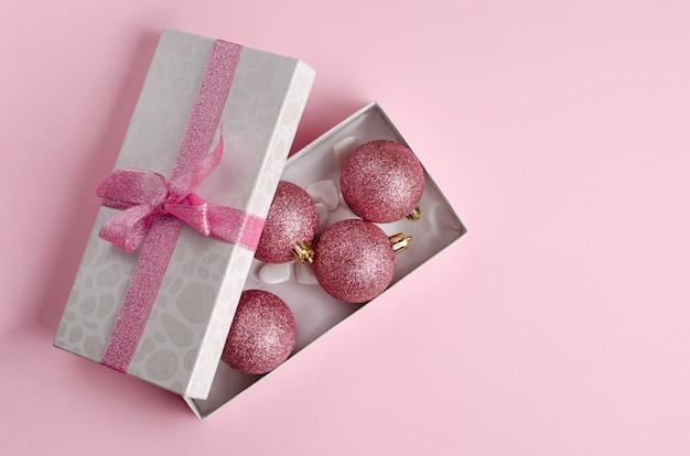Composição minimalista de natal. caixa de presente aberto com enfeites em rosa pastel. apartamento leigos copyspace. .
