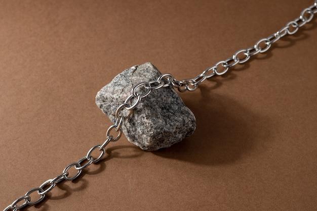 Composição minimalista de natureza morta em marrom bege com material natural: corrente de pedra e aço, conceito de design de arte moderna abstrata, visão lateral