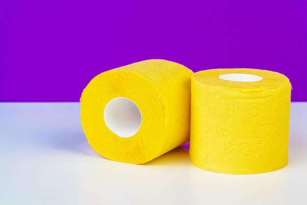 Composição minimalista de papel higiênico amarelo brilhante rola no roxo