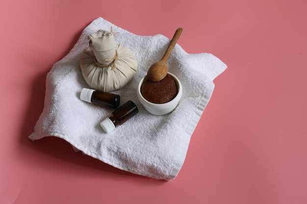 Composição minimalista de spa com saco de massagem de ervas, frascos de esfoliante natural e óleo no fundo rosa, copie o espaço.