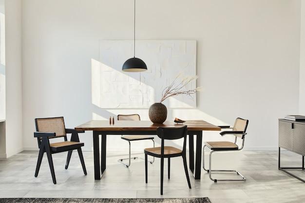 Composição minimalista do interior da sala de jantar com mesa de madeira, cadeiras de design, flores secas em um vaso, abajur preta, pinturas de arte na parede e acessórios pessoais elegantes.