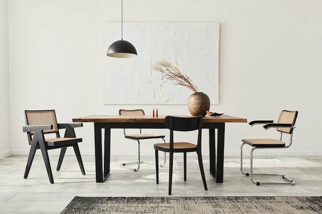 Composição minimalista do interior da sala de jantar com mesa de madeira, cadeiras de design, flores secas em um vaso, luminária preta, pinturas artísticas na parede e acessórios pessoais elegantes.