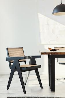 Composição minimalista do interior da sala de jantar com mesa de madeira, cadeiras de design, flores secas em um vaso, luminária preta, pinturas artísticas na parede e acessórios pessoais elegantes