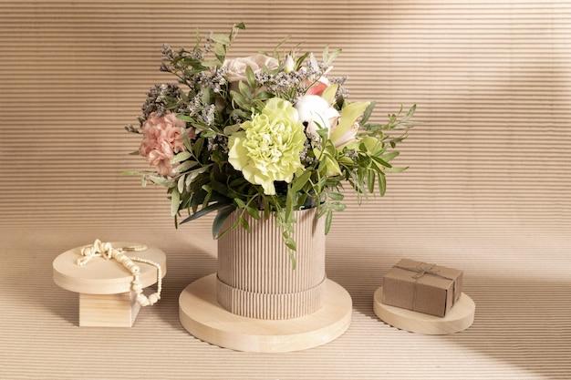 Composição minimalista ecológica monocromática com bouquet de flores e suportes de madeira de diferentes formas com caixa de presente diy e missangas em bege com sombras.