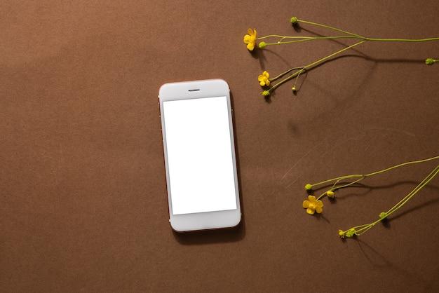 Composição minimalista vida marrom bege com flores silvestres e tecnologia celular flor amarela a ...