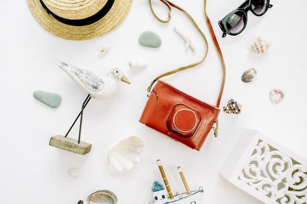Composição moderna com estatueta de pássaro, barco de brinquedo, câmera retro, óculos de sol, conchas e chapéu de palha na superfície branca