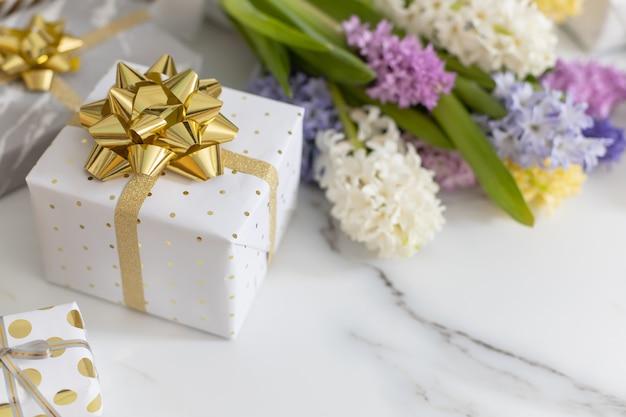 Composição moderna com laço de fita de caixas de presente embrulhado festivo decorado por flores
