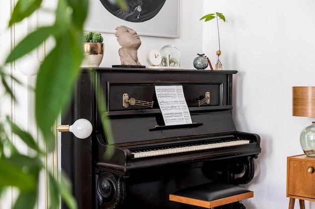 Composição moderna do interior da casa com um piano preto elegante, móveis de design, carpete, cactos, plantas, decoração, pinturas de simulação e acessórios pessoais elegantes na decoração da casa.