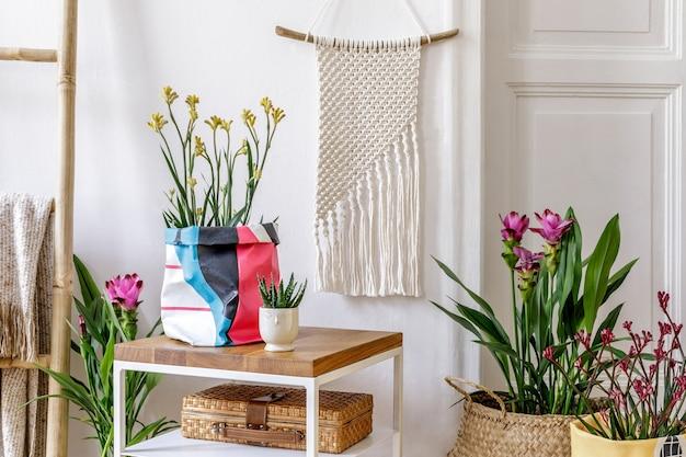 Composição moderna do interior do jardim com mesa de centro de madeira, muitas plantas e flores em vasos de design, escada, decoração de vime, macramê, acessórios pessoais na decoração elegante da casa.