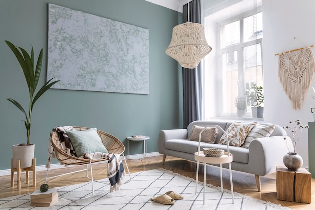 Composição moderna e boêmia de design de interiores com sofá cinza, poltrona de rattan, cubo de madeira, travesseiro xadrez, plantas tropicais, mesa pequena e acessórios elegantes
