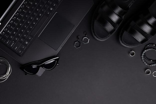Composição monocromática com laptop, roupas e acessórios