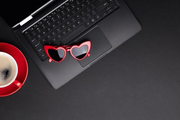 Composição monocromática de vista plana leiga superior com laptop, xícara de café e óculos de sol