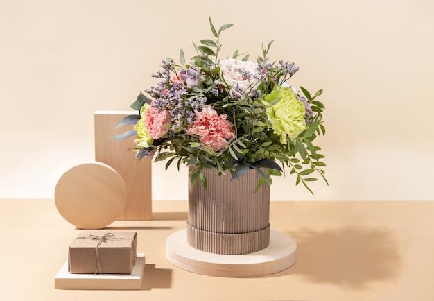 Composição monocromática mínima ecológica com buquê de flores e suportes de madeira de diferentes formas com caixa de presente diy em fundo bege com sombras.