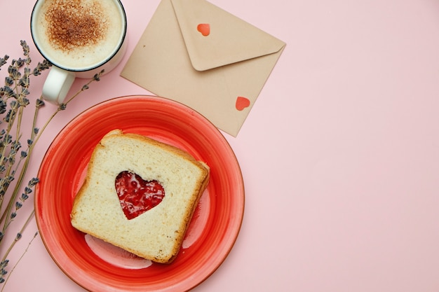 Composição para cartão de dia dos namorados com café, enveloope e sanduíche em forma de coração