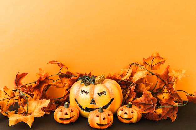 Composição para halloween com folhas e abóboras sorridentes
