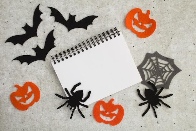 Composição para o halloween com caderno branco, aranhas decorativas, abóboras, teias de aranha e morcegos no fundo cinza. copie o espaço. vista do topo.