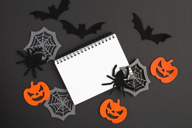 Composição para o halloween com caderno branco, aranhas decorativas, abóboras, teias de aranha e morcegos no fundo preto. copie o espaço. vista do topo.