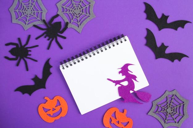 Composição para o halloween com caderno branco, bruxa decorativa, aranhas, abóboras, teias de aranha e morcegos no fundo roxo. copie o espaço. vista do topo.
