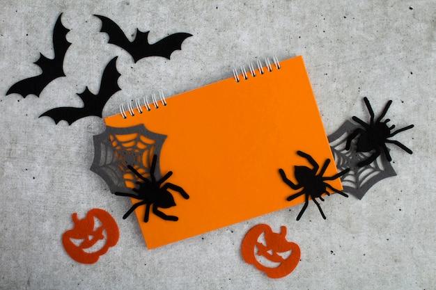 Composição para o halloween com caderno laranja, aranhas decorativas, abóboras, teias de aranha e morcegos no fundo cinza. copie o espaço. vista do topo.