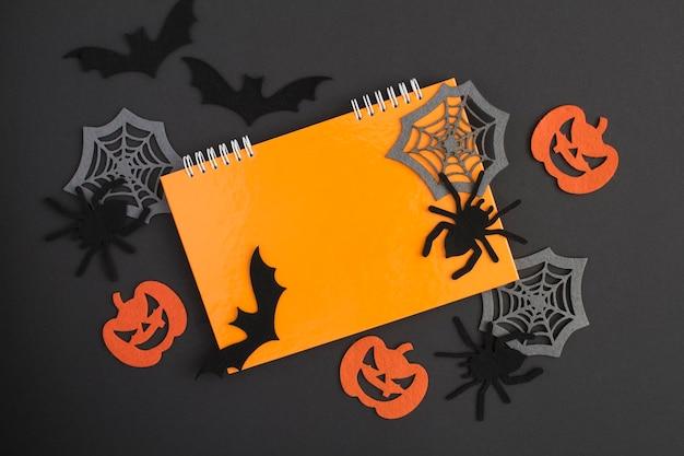 Composição para o halloween com caderno laranja, aranhas decorativas, abóboras, teias de aranha e morcegos no fundo preto. copie o espaço. vista do topo.