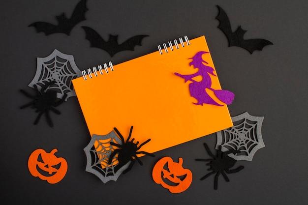 Composição para o halloween com caderno laranja, bruxa decorativa, aranhas, abóboras, teias de aranha e morcegos no fundo preto. copie o espaço. vista do topo.