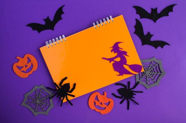 Composição para o halloween com caderno laranja, bruxa decorativa, aranhas, abóboras, teias de aranha e morcegos no fundo roxo. copie o espaço. vista do topo.