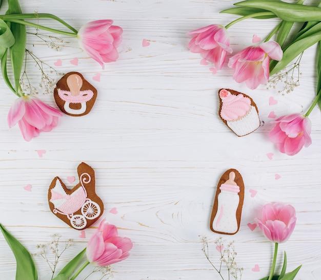 Composição para recém-nascidos em um fundo de madeira com tulipas cor-de-rosa, corações e um biscoito