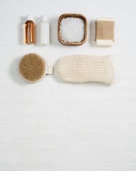 Composição plana com acessórios de banho com pequenos frascos com gel e xampu, sabonete, sal marinho, toalha de rosto