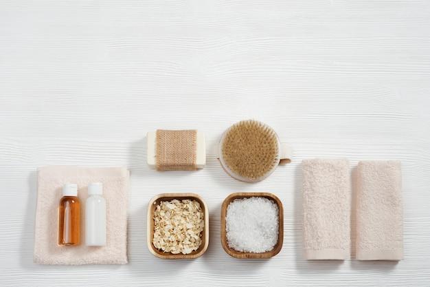 Composição plana com acessórios de banho com toalhas de algodão frascos pequenos com gel e sabonete shampoo sal marinho