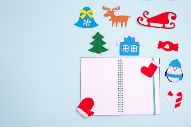 Composição plana com bloco de notas em branco aberto e brinquedos de natal luva de sino pinguim abeto casa na árvore veado trenó meia de gengibre
