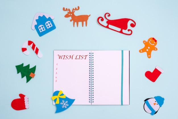 Composição plana com caderno aberto em branco com letras da lista de desejos e decorações de natal