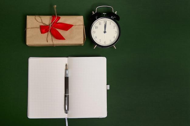 Composição plana com caneta em bloco aberto com folhas em branco vazias, despertador e um presente em papel de embrulho artesanal com laço amarrado e fita vermelha em fundo verde escuro com espaço de cópia para anúncio