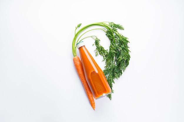 Composição plana com cenouras frescas maduras e suco de cenoura isolado