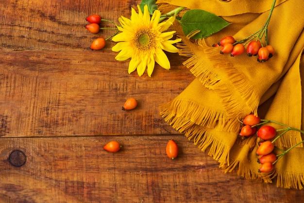 Composição plana com lenço de malha amarelo, bagas de roseira brava e girassol em uma mesa de madeira. outono acolhedor ou o conceito de descanso de inverno. lugar para texto, quadro, vista superior, espaço de cópia, layout