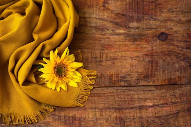 Composição plana com lenço de malha amarelo e girassol em uma mesa de madeira. outono aconchegante ou o conceito de descanso de inverno