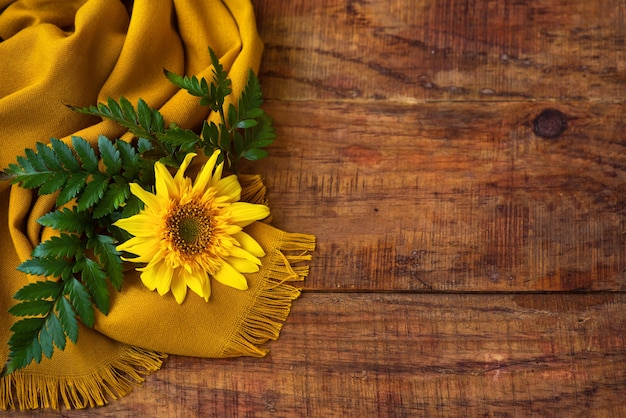 Composição plana com lenço de malha amarelo, galho verde e girassol em uma mesa de madeira