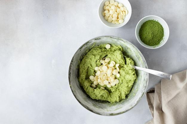 Composição plana com massa matcha de chá verde, gotas de chocolate, ovos