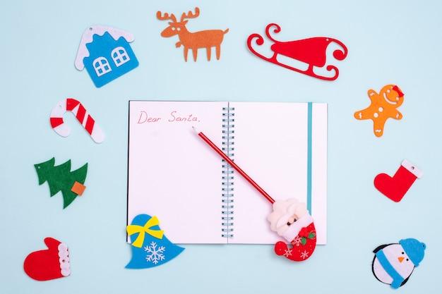 Composição plana com um caderno aberto vazio com a inscrição querido papai noel, uma caneta com papai noel e decorações de natal de feltro