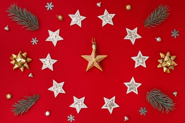 Composição plana de decorações de natal em branco e ouro e ramos de abeto, sobre um fundo vermelho.